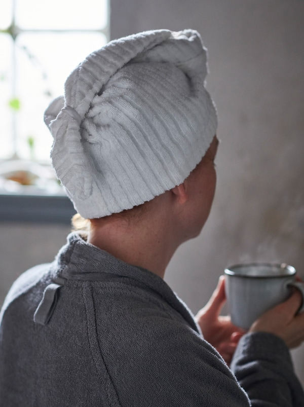 En kvinna i en badrock och med håret i en TRÄTTEN hårhandduk håller i en temugg i en badrumsmiljö.
