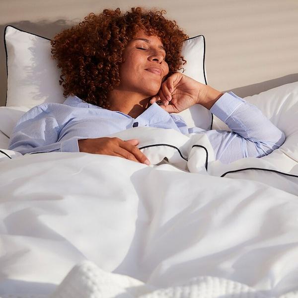 En kvinna i ljusblå pyamas sover i en säng med vita KUNGSBLOMMA sängkläder