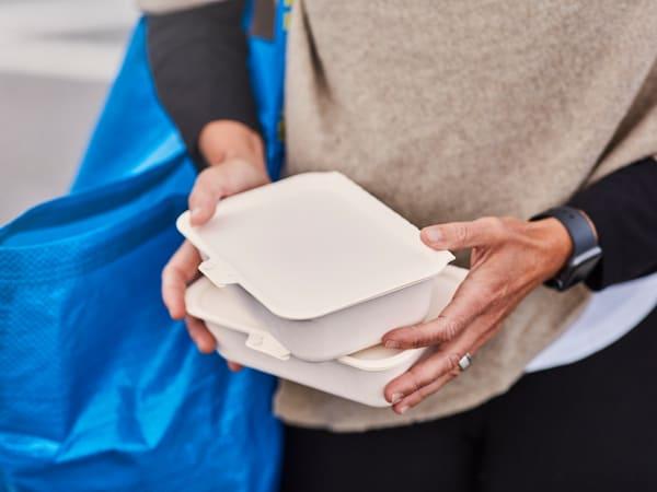 En kvinna klädd i beige tröja bär på två take-away boxar, över axeln har hon en blå IKEA kasse