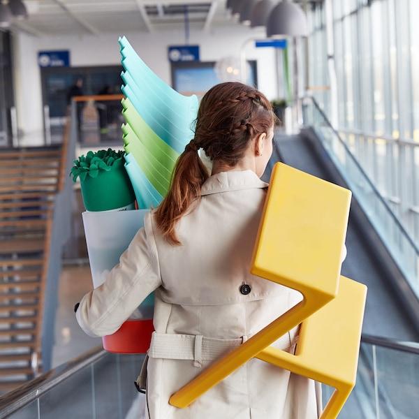 En kvinna kliver på ett rullband och bär på massor av produkter som hon köpt på IKEA.
