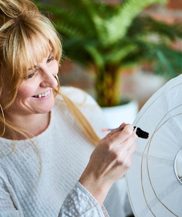 En kvinna med blont hår håller i en stor, vit papperslampskärm och målar svarta linjer på den med hjälp av en tunn målarpensel.
