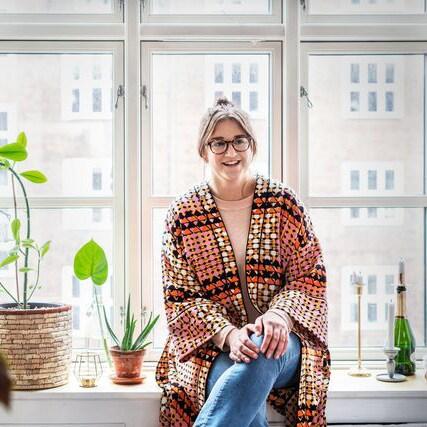 En kvinna sitter i en fönsterkarm.