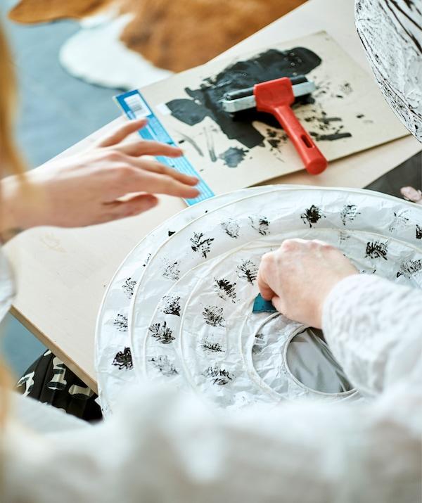En kvinna skapar ett mönster med ormbunksblad på en vikt, vit papperslampa genom att trycka dit mönstret med en stämpel doppad i svart färg.