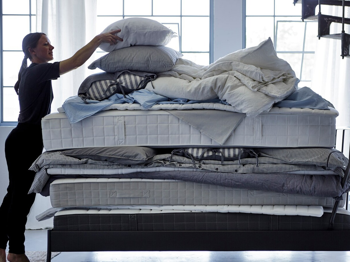 En kvinna som lägger en kudde ovanpå en hög med mjuka madrasser, täcken och sängkläder.