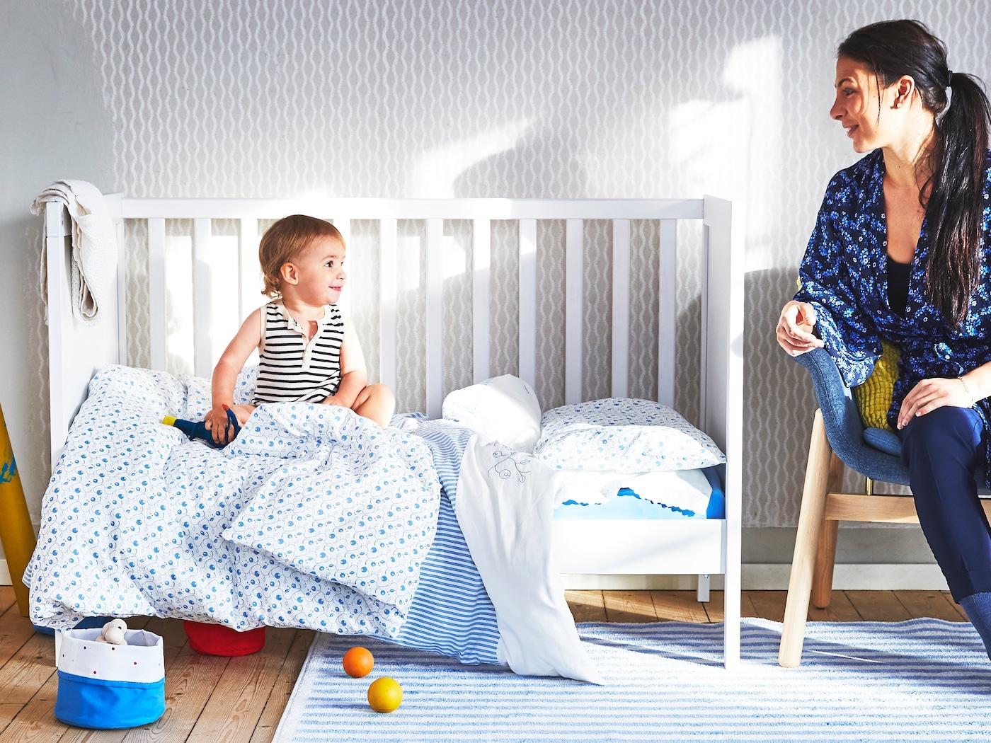 En kvinna tittar på en bebis på en säng med blå och vita GULSPARV barntextilier. En randig GULSPARV matta är i förgrunden.