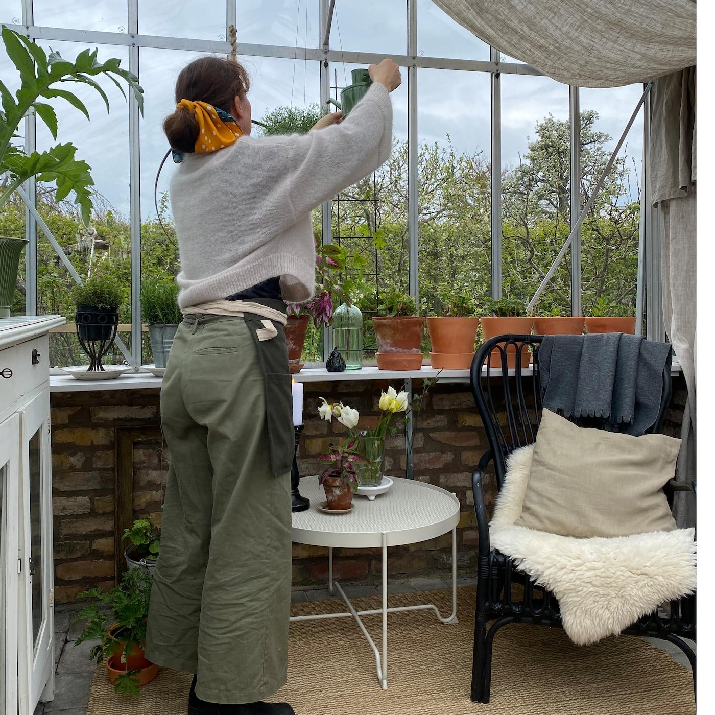 En kvinna vattnar växterna i sitt mysigt inredda växthus.