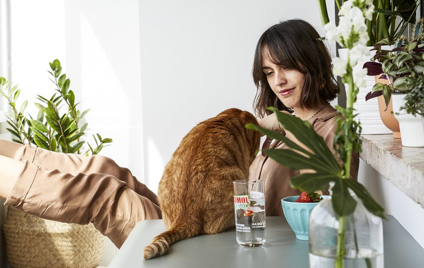 En kvinne og en katt sitter ved et bord på en hvit balkong med mange potteplanter.