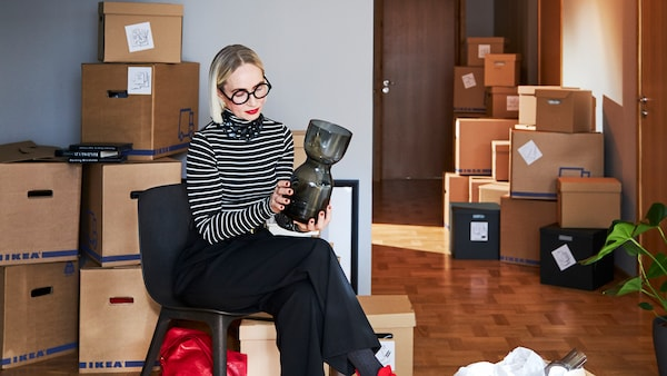 En kvinne sitter på en svart stol i et rom med stabler av IKEA-pappesker, mens hun kikker på en grå glassvase som hun holder i hendene.