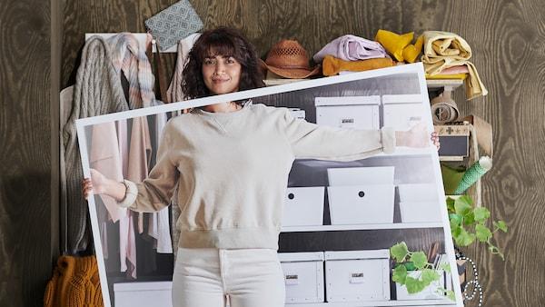 En kvinne som holder opp et bilde foran seg om hvor ryddig hyllen kan bli.