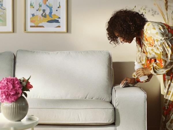 En kvinne som vasker bort en flekk fra sofaen sin.