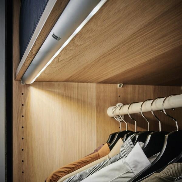 En LED lysskinne integreret i et garderobeskab. Lyset skinner lige ned på tøjet på bøjlerne.