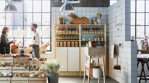 En liten butik fylld med grönsaker i stora trälådor, trähyllor fyllda med kaffe och kakel på väggarna