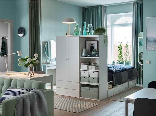 En lugn och ljusgrön enrumslägenhet med gröna gardiner, en grön soffa och en vit sängstomme med förvaring.