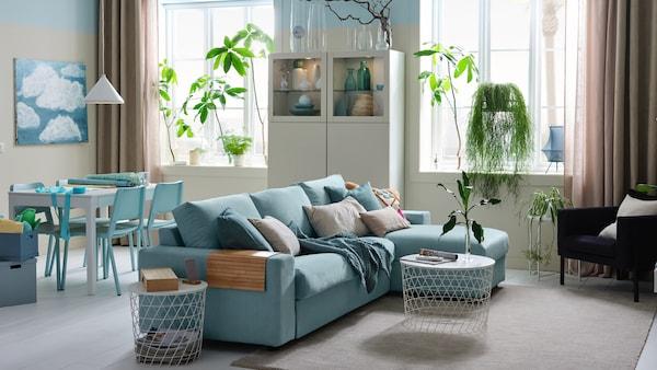 En lys etværelses med en 3-pers. sovesofa med chaiselong, en hvid opbevaringsløsning og et spiseområde.