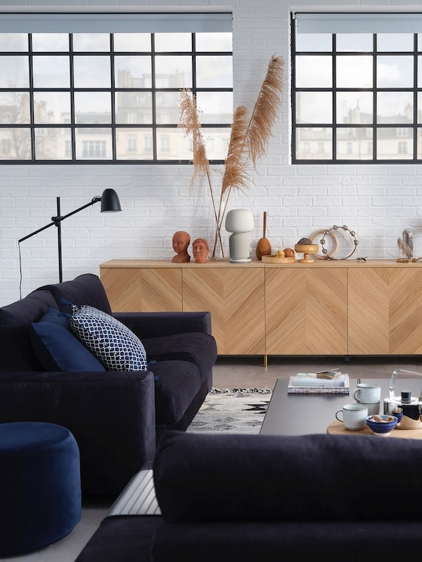 En lysegrøn sofa omgivet af naturmaterialer og lyseblå væg i baggrunden.