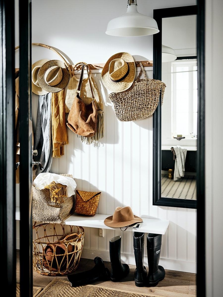 En MACKAPÄR benk med oppbevaring med ei grå pute ved et MACKAPÄR skap med en vase og et sjal i en entré.