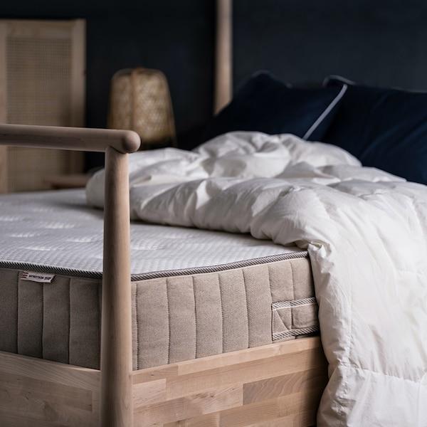 En madras ligger i et sengestel af træ. Der er ikke rullemadras eller lagen på madrassen og der ligger en dyne uden betræk og to hovedpuder på den.