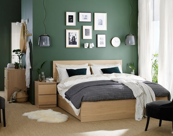 En MALM dobbeltseng i træfiner står mellem to MALM sengeborde/kommoder med to skuffer i et soveværelse med mørkegrønne vægge og godt lysindfald udefra.