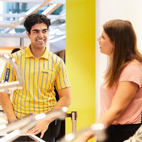 En man i IKEA uniform hjälper en kund klädd i rosa tröja.