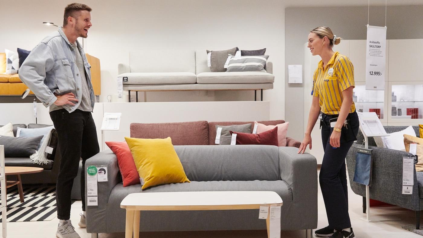 En man klädd i jeansjacka och en kvinna klädd i IKEA unfirom pratar med varandra. På bilden syns en grå soffan med en röd och en gul kudde i.
