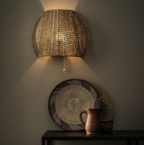 En MÅNALG væglampe i søgræs hænger op af en væg i jordfarve og kaster lys. Neden under står en kande, en bakke og en vase,