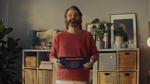 En mand med en gammel vinylplade står foran sine genvunde KALLAX reoler, der har fået en chance til.