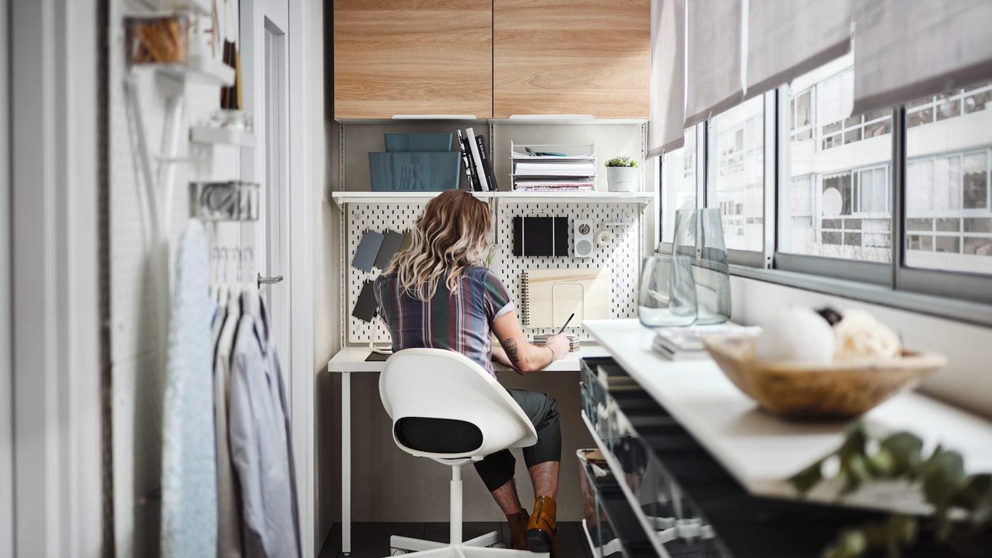 En mand på en beige/hvid skrivebordsstol ved et hvidt skrivebord med et hvidt opbevaringssystem ovenover, indrettet på en lukket altan.