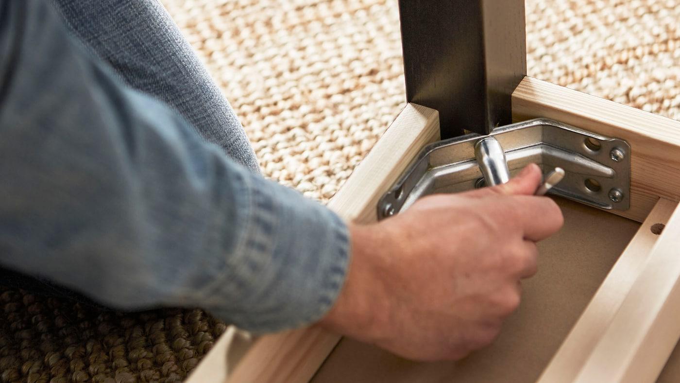 En mandehånd er ved at skrue et beslag på et bord, der ligger på hovedet.