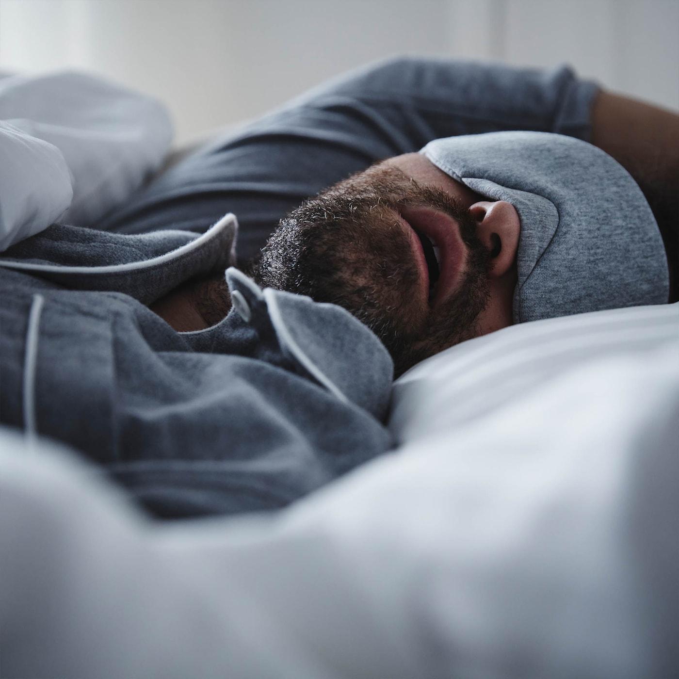 En mann med blå pyjamas og matchende øyemaske ligger i senga og sover med munnen åpen.