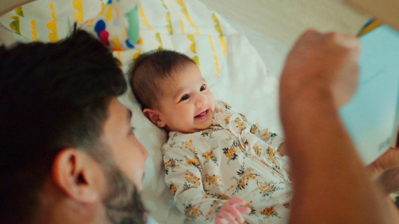 En mann med skjegg leker med en smilende baby i ei seng.