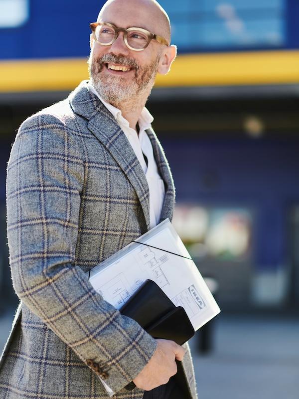 En mann med skjegg og briller holder ei mappe med IKEA-dokumenter.