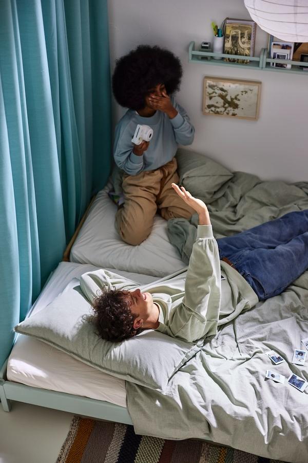 En mann og en kvinne på to senger med grønnstripet BERGPALM og lysegrått melert SPJUTVIAL sengetøy ved en gardin.
