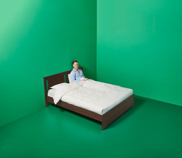 En mann sitter i ei mørk treseng med hvitt sengetøy i hjørnet av et grønt rom.