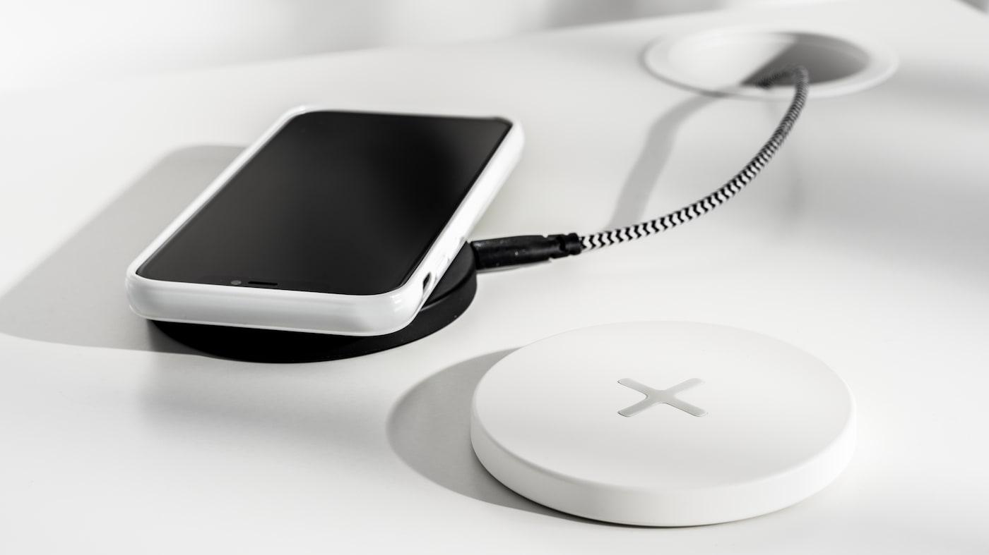 En mobiltelefon som ligger på en svart platta för trådlös laddning, bredvid finns en vit platta för trådlösladdning.