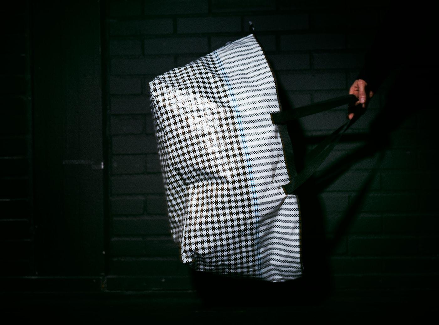 En modell håller i en SAMMANKOPPLA kasse i ett mörkt rum. Den blanka ytan och hundtandsmönstret lyses upp av kamerablixten.