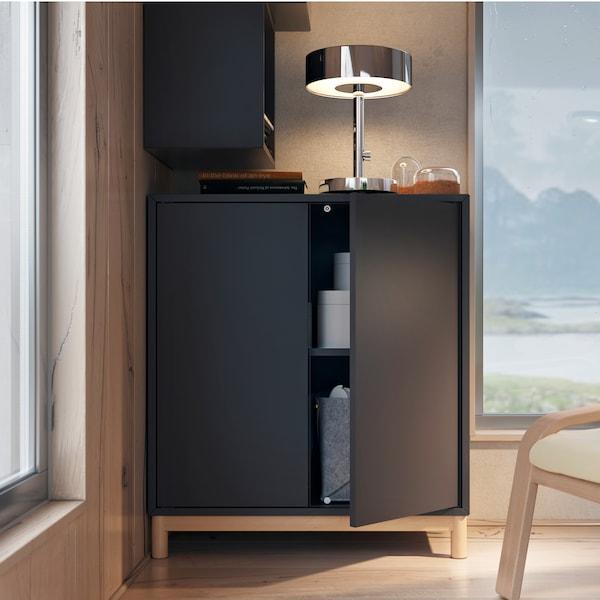 En mörkgrå EKET skåpkombination med ben och en flyttbar hylla. En lampa står på den och det finns ett fönster bredvid med en panoramautsikt.
