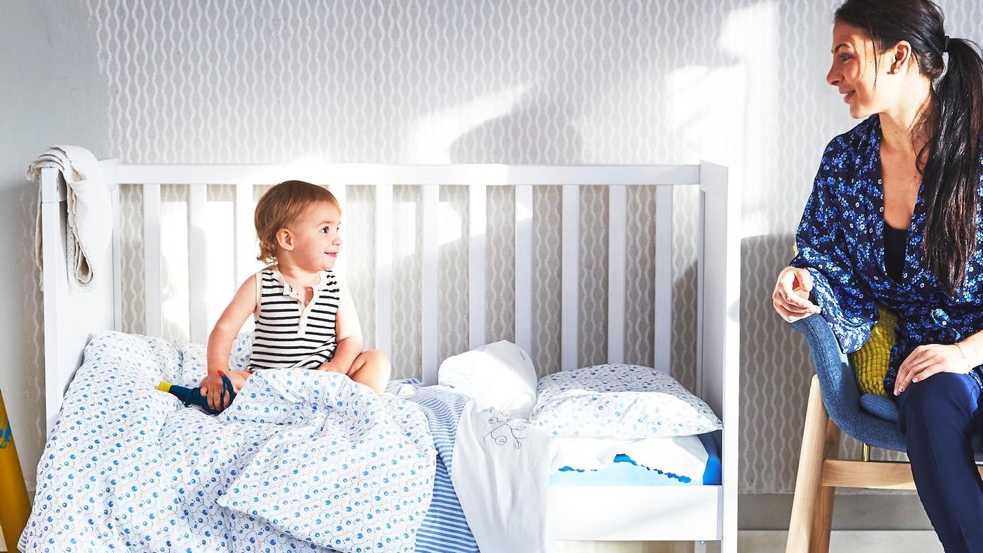 En mor sitter på en trestol og ser på babyen sin som sitter i en hvit og åpen sprinkelseng med blå tekstiler.
