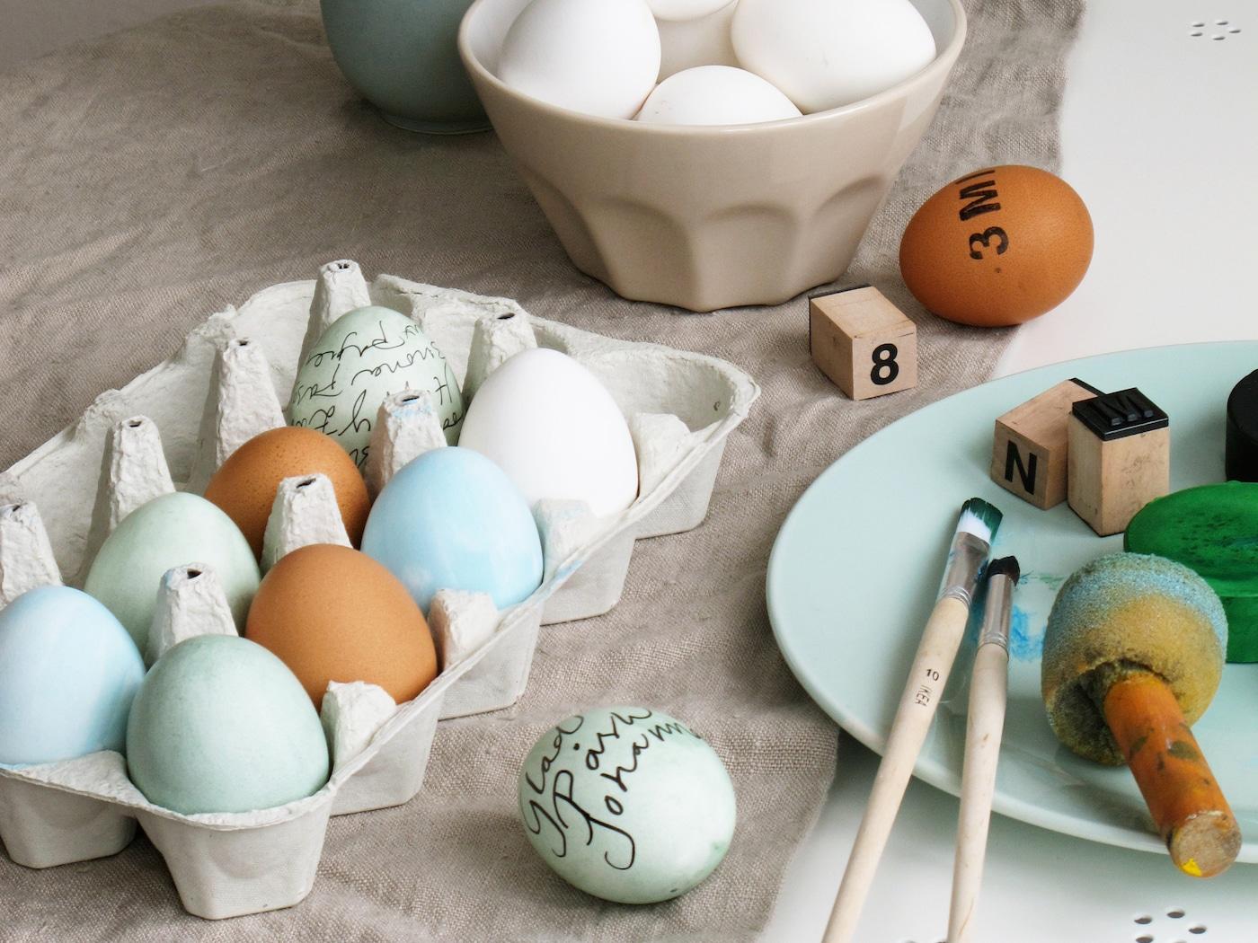 En öppen äggkartong med färgade ägg och en skål med ofärgade ägg står på en duk på ett bord. På bordet finns även ett fat där det ligger penslar och stmplar. På några av äggen har man skrivit, ritat och stämplat.