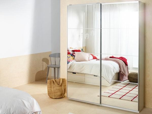 En PAX garderob med spegeldörrar i ett ljust sovrum