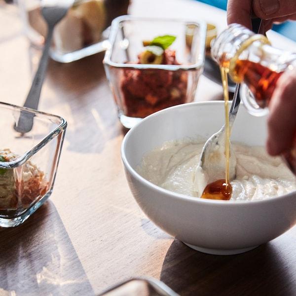 En person hælder olie i en skål med andre ingredienser