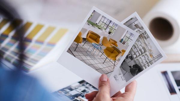 En person holder billeder af mulige indretningsløsninger