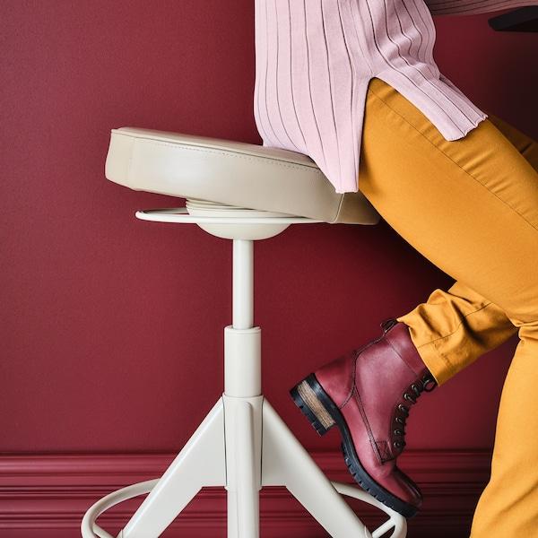 En person i gula byxor och röda stövlar som sitter på ett beige TROLLBERGET aktivt sitt-/ståstöd vid en vinröd vägg.