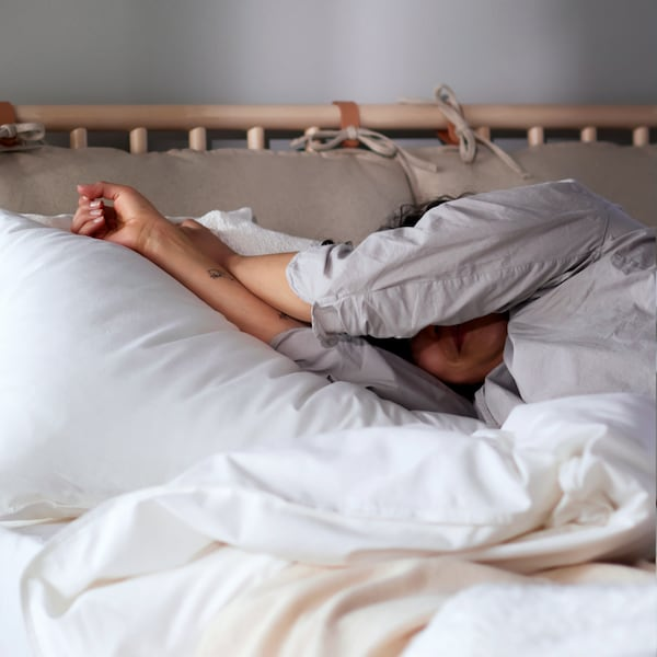 En person i pysjamas ligger i en BJÖRKSNÄS-seng i bjørk redd opp med hvitt ÄNGSLILJA-sengesett.