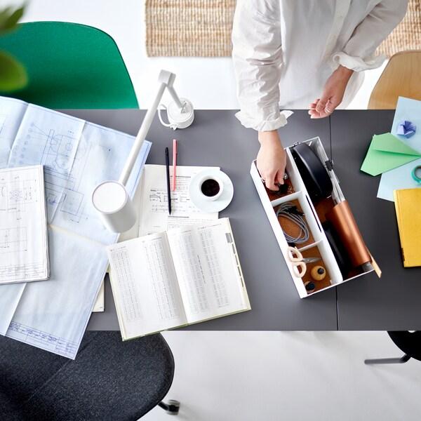 En person lägger ner något i ett vitt KVISSLE skrivbordsställ på ett grått skrivbord intill några papper och en arbetslampa.