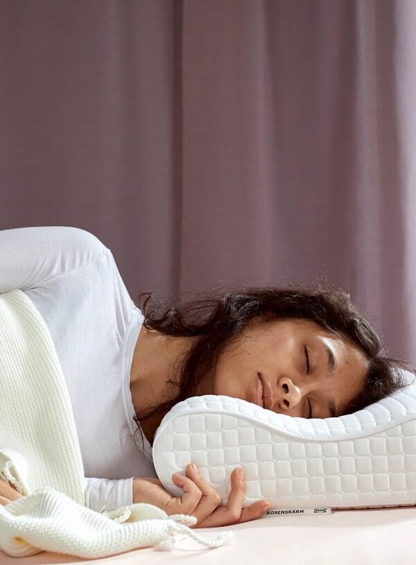 En person ligger og sover med hovedet på en ergonomisk hovedpude.