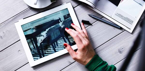 En person med rød neglelak ser på møbler på en tablet.