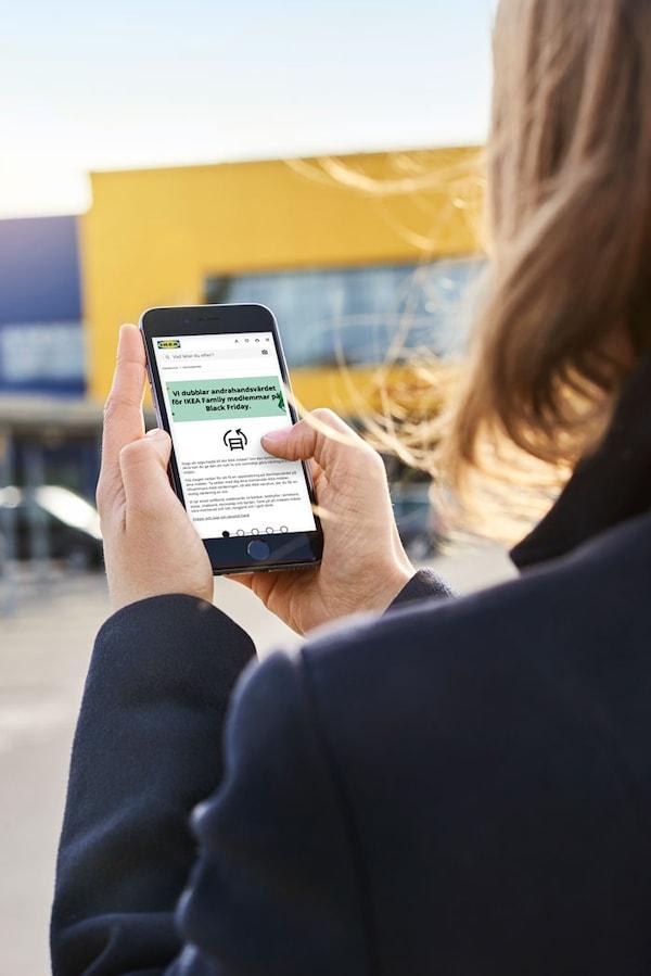 En person står med ryggen mot kameran och håller en svart iphone med buy back-verktyget öppet i mobilen.