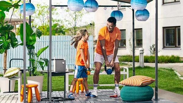 En pige og hendes far løfter vægte i en gårdhave med en GUNNÖN pavillon, RUNNEN udendørs gulvfliser og solcelledrevne lamper.