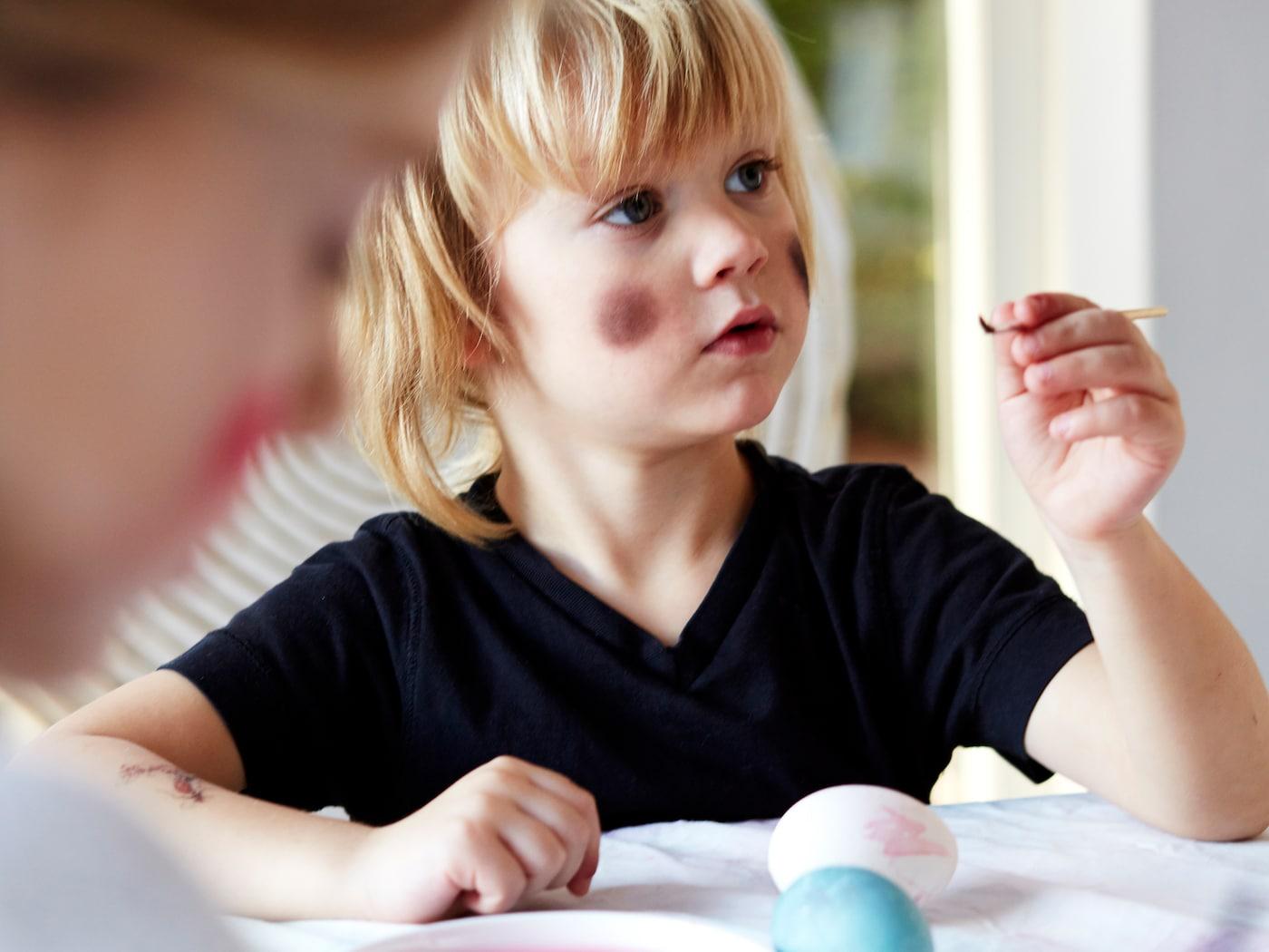 En pojke i svart t-shirt med målade kinder som en påskkärring sitter vid ett bord och målar ägg.