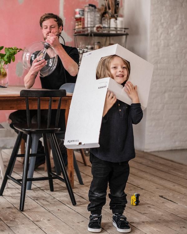 En pojke står framför ett matbord med en kartong över huvudet och tittar ut genom en öppning i kartongen. Pappan sitter vid matbordet och monterar en lampa.